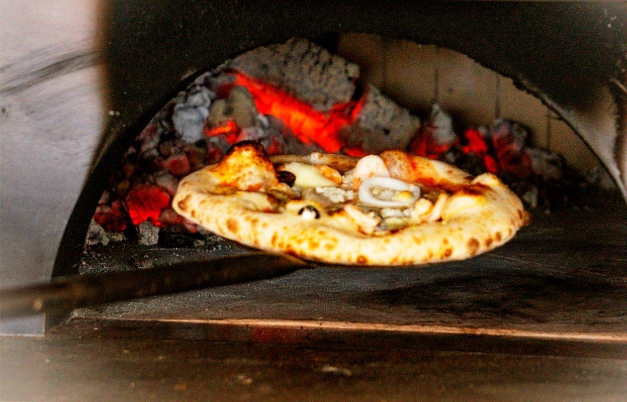 コエナの石窯で焼かれるピザ