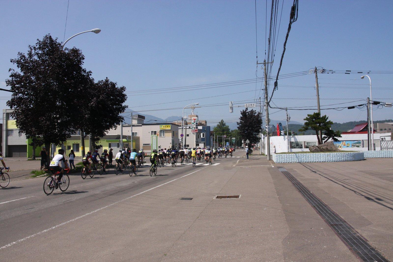 倶知安町役場の前を疾走するヒルクライム参加者たち
