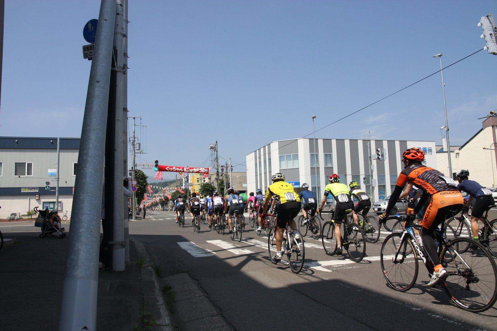 じゃが祭りの会場をパレード走行する自転車選手たち