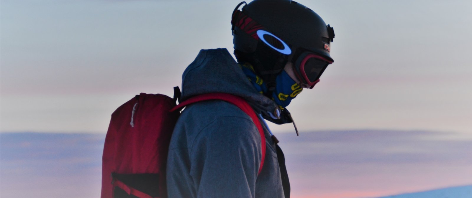 Man standing on the mountains during sunset with oakley goggles and red backpack