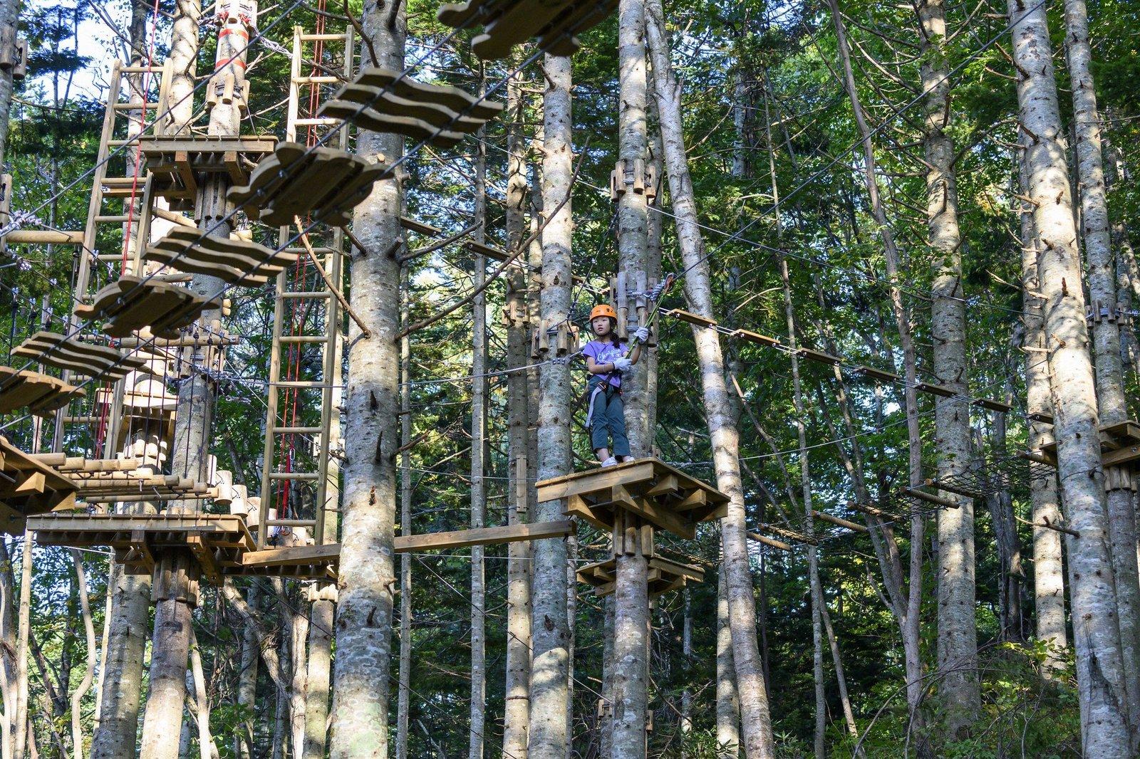 A girl challenging Hanazono Forest Tree Trekking course in Niseko