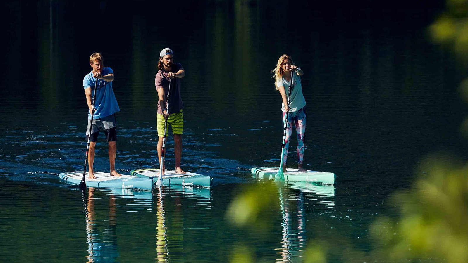 People paddling stand up paddle board on calm water