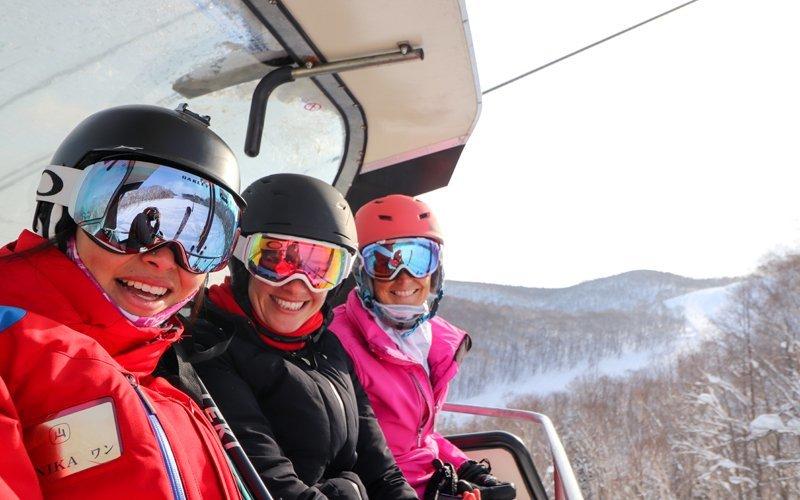 微笑在滑雪電纜車的三名婦女