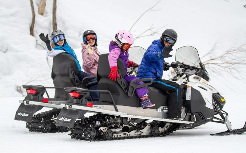 family having fun on a hanazono snowmobile tour