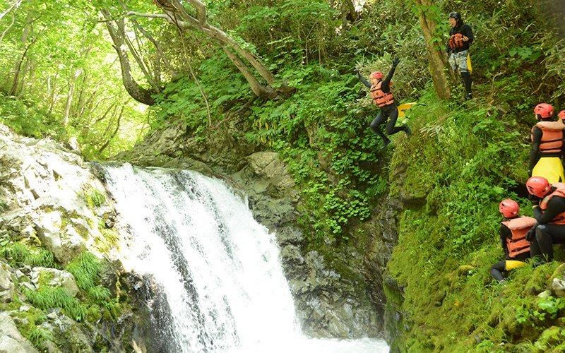 キャニオニングで滝壺にダイブする人々
