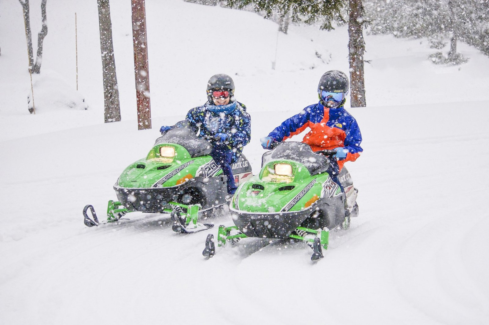 Two boys racing on kids snowmobiles in Hanazono, Niseko