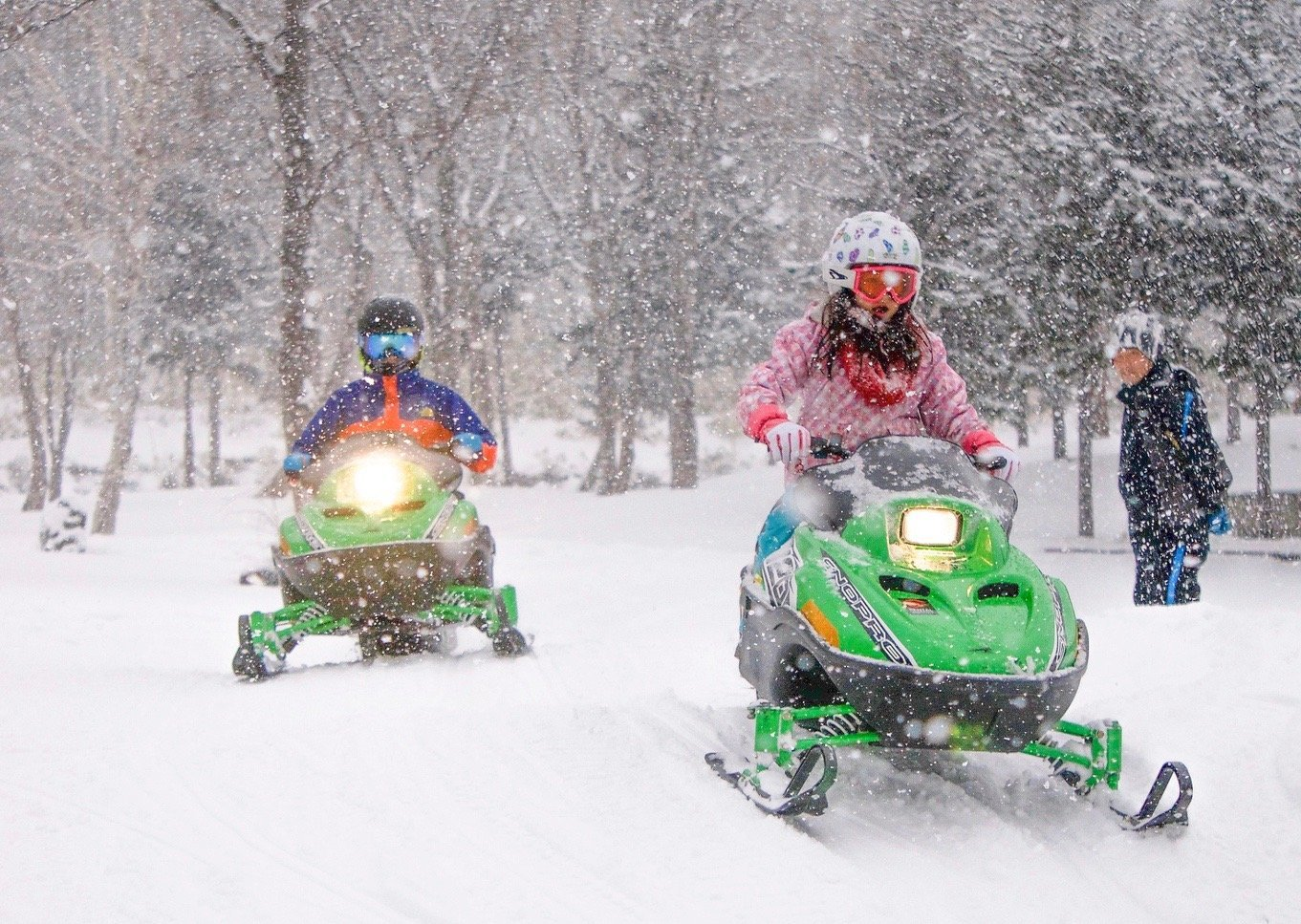 2 children driving snowmobiles together