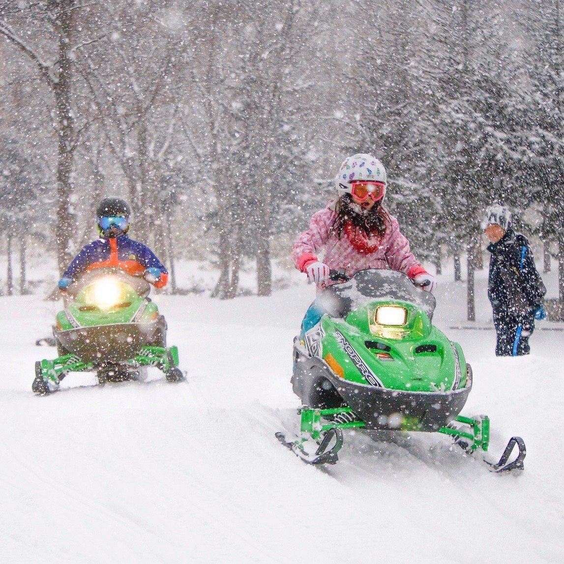 ニセコで子供用スノーモービルを運転する子供