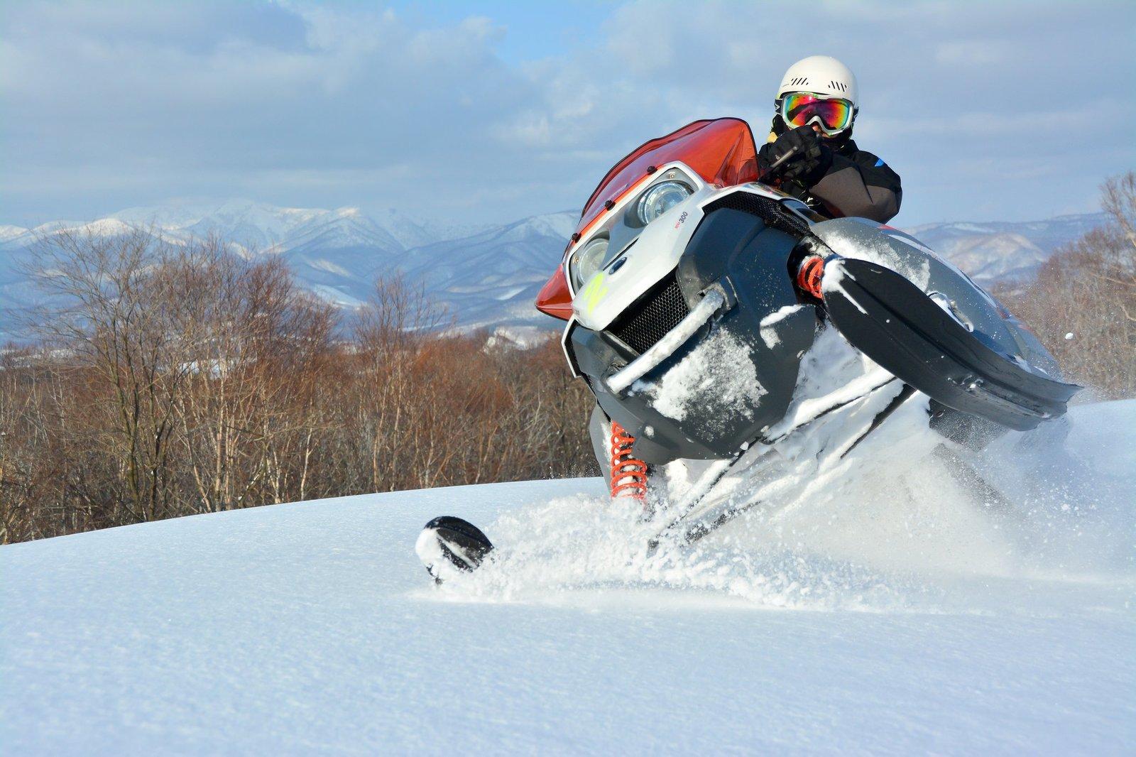 花園スキーリゾートでスノーモービルを運転する人