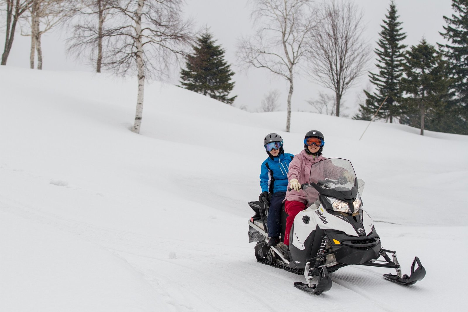 A family riding tandem on snowmobile in Niseko Hanazono resort