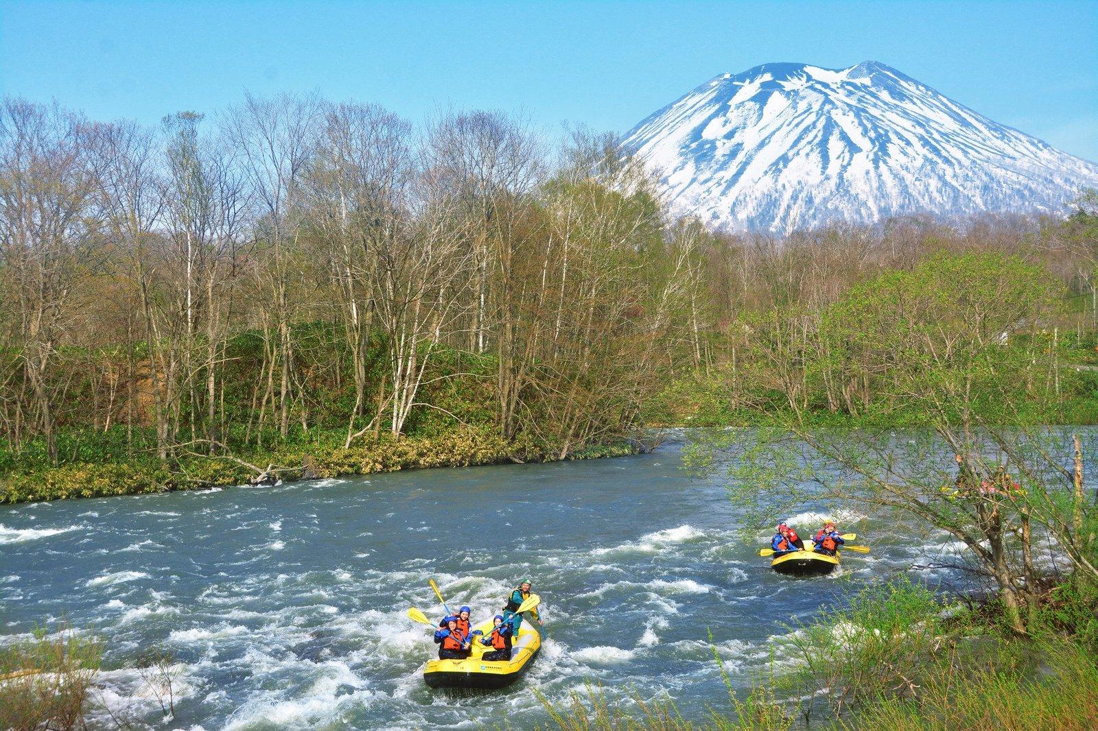 羊蹄山に向かってラフティングボートをこぐ人々