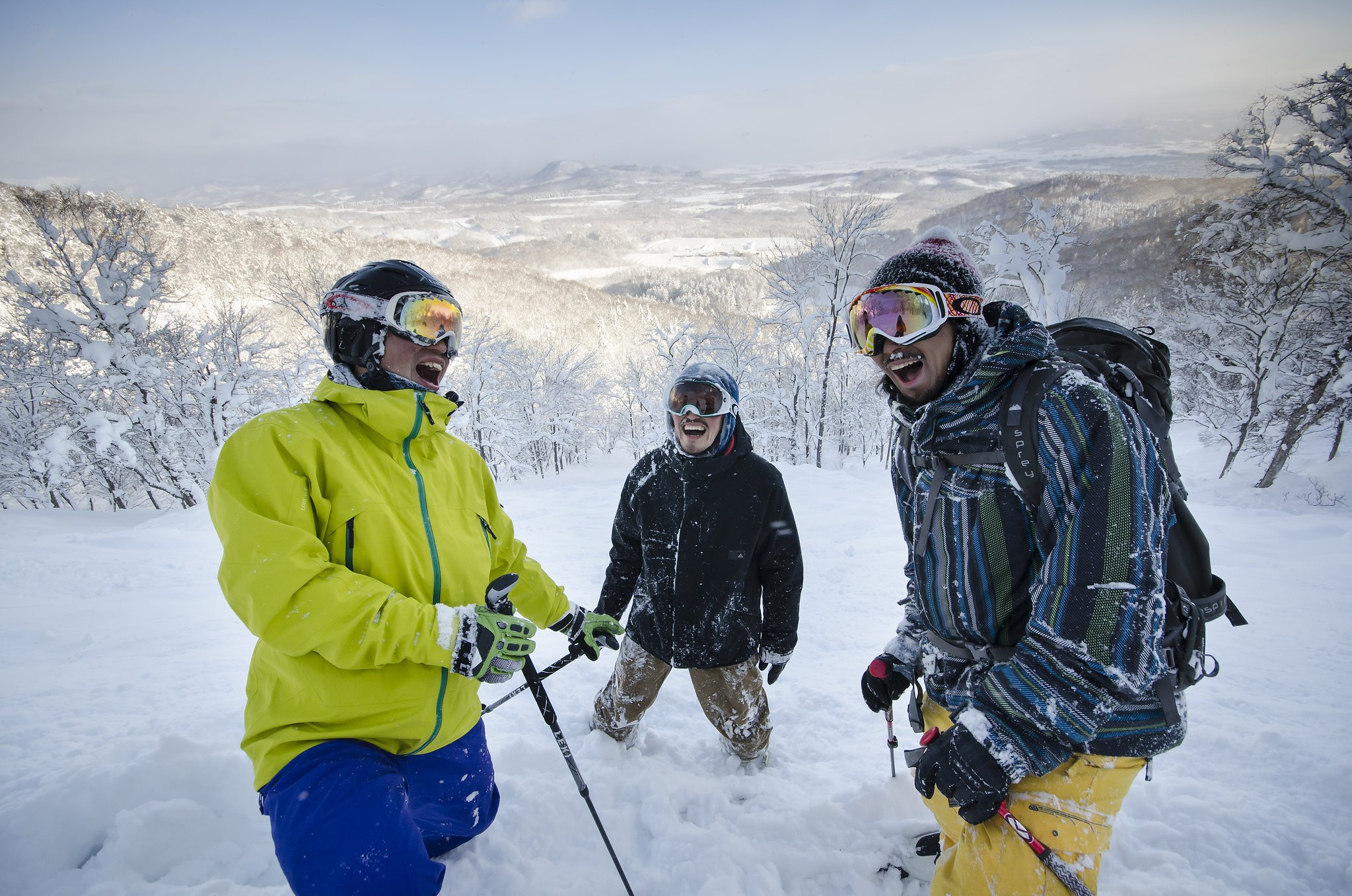 3 men laughing in the deep powder snow of Hanazono, Niseko.