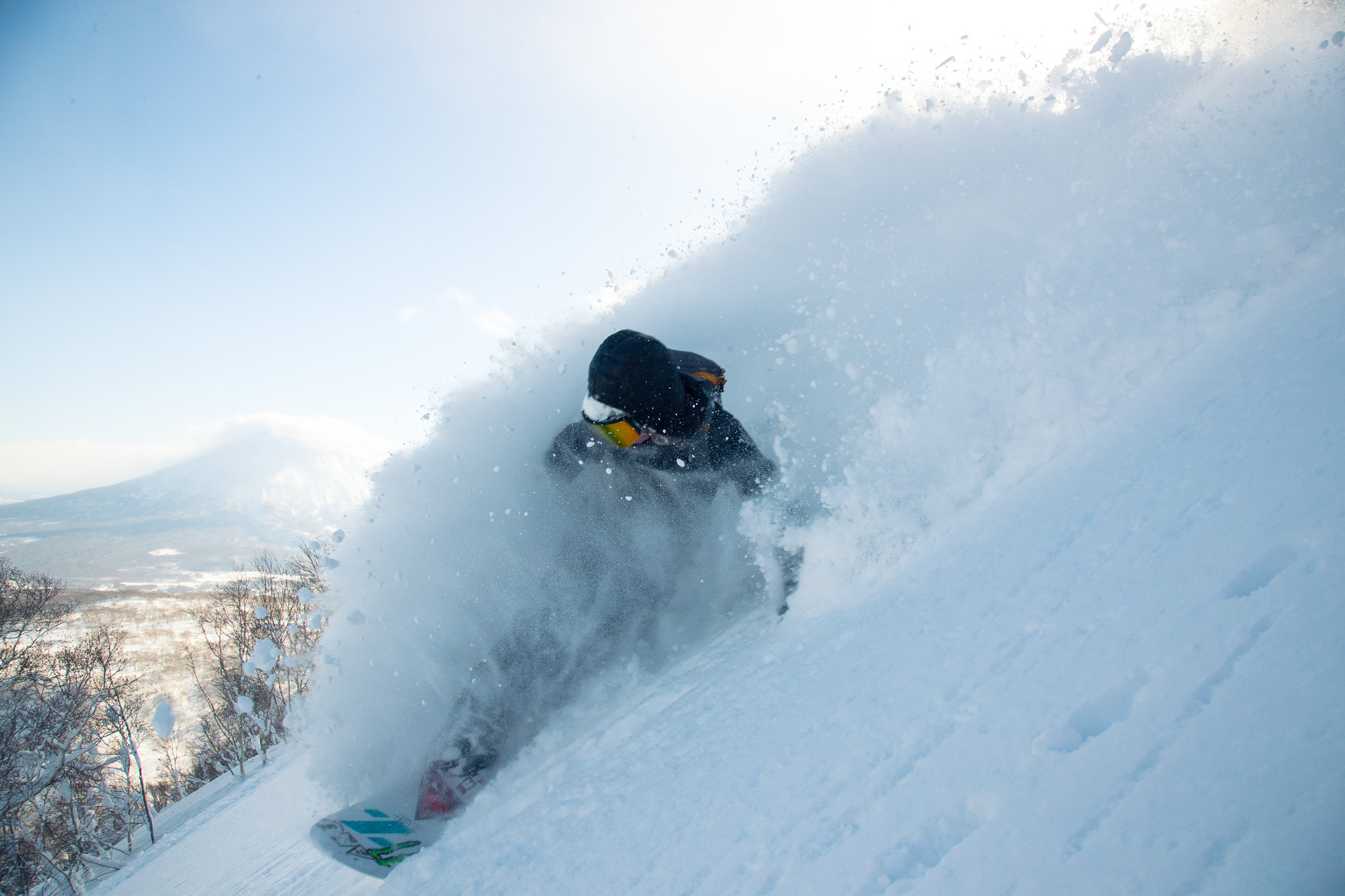 A snowboarder deep in powder in Niseko, Japan.